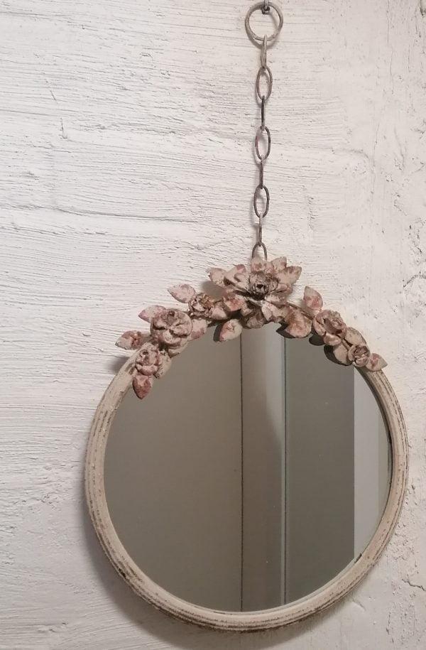 Kukkakoristeltu peili ripustusketjulla.